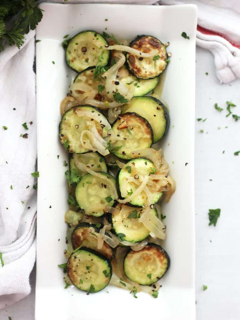 Sautéed zucchini and onions in a white dish garnished with fresh parsley and black pepper.