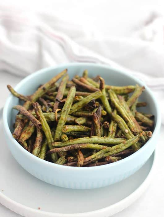 Air fried green beans served in a bowl in front of a white cloth.