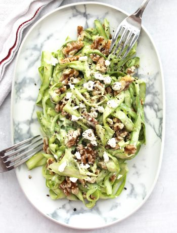 Overhead shot of a shaved asparagus salad on a plate with two forks.