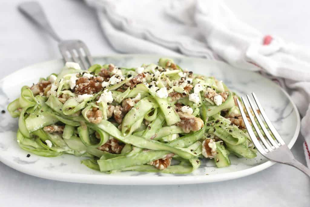 Asparagus, goat cheese and walnut salad on a white plate with two forks.
