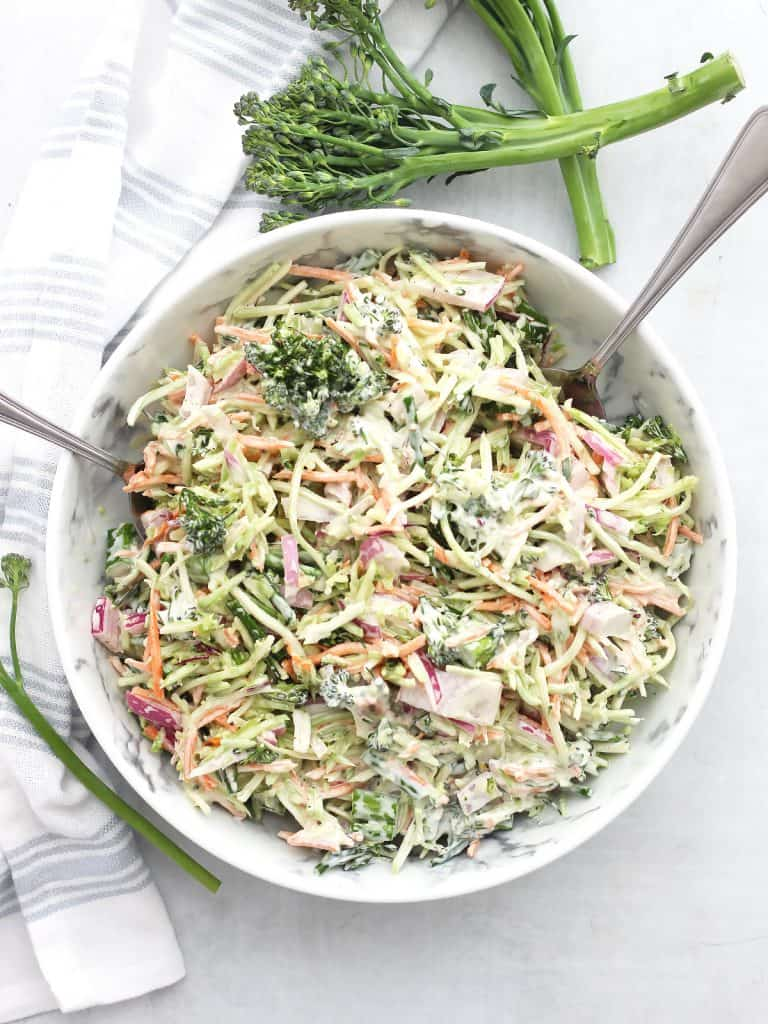 Overhead shot of broccolini slaw in a bowl next to fresh broccolini stems.