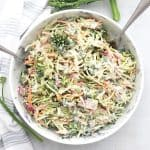 Broccolini coleslaw in a serving bowl with two spoons.