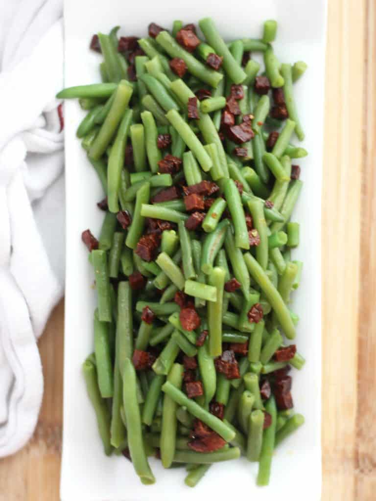 Green beans and chorizo served on a long white dish.
