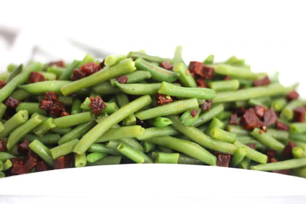 Close of of cooked green beans with diced chorizo.