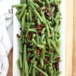Overhead shot of green beans with chorizo on a white serving plate.