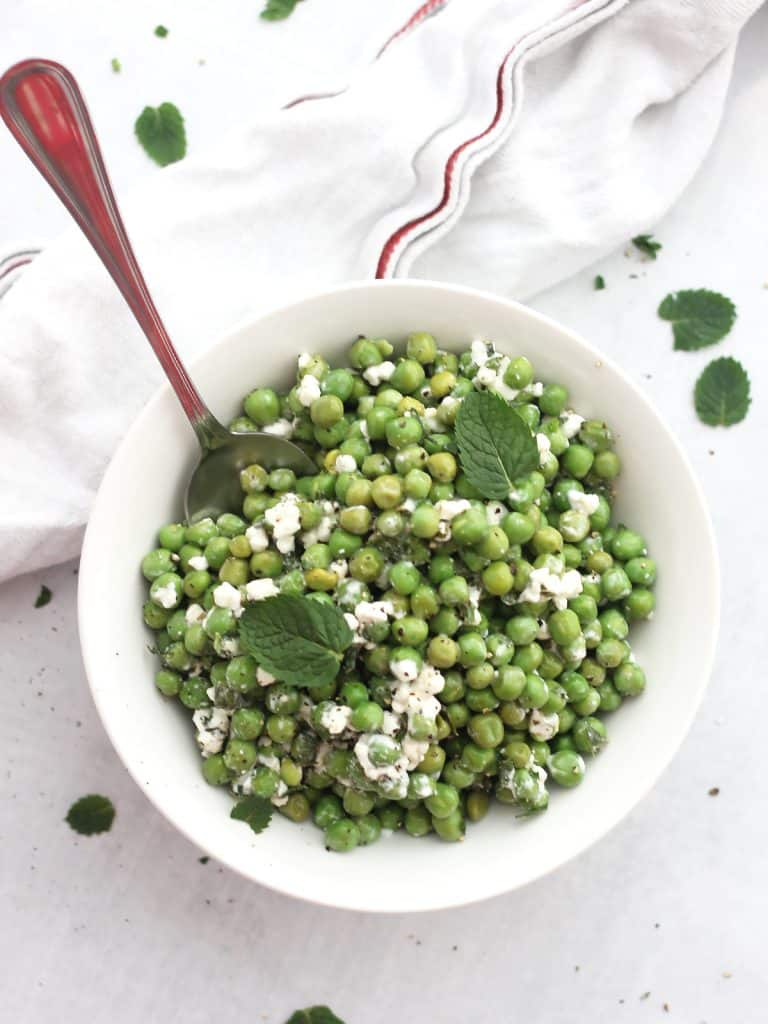 Pea mint and feta salad in a white bowl with a spoon.