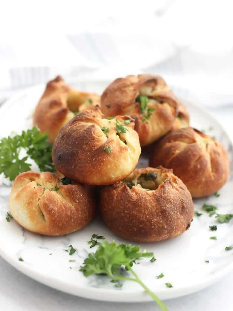 Pizza dough garlic balls on a serving plate garnished with parsley.