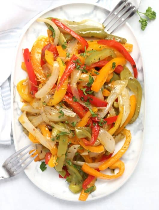 Overhead shot of sautéed peppers and onions on a plate with two forks.