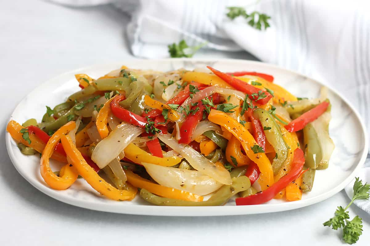 Sliced bell peppers and onions on a serving plate.