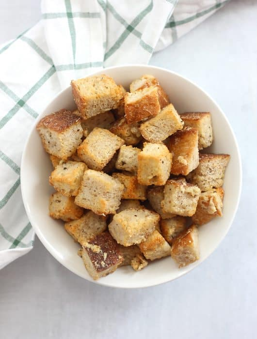 Air fryer parmesan croutons in a white bowl next to a white and green cloth.