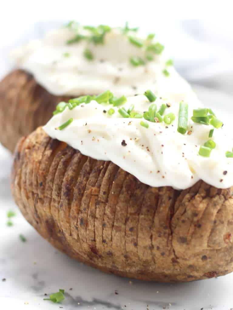 Close up of the sour cream and chive topping on the cooked potato.
