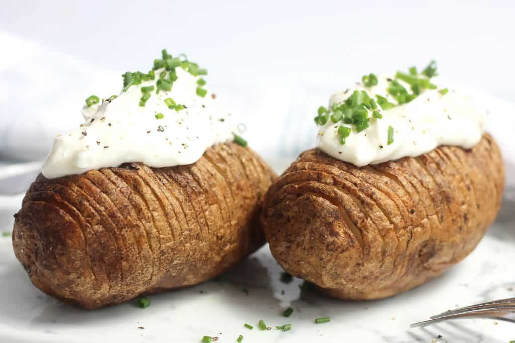 Two air fryer haselback potatoes on a plate with sour cream and chives.