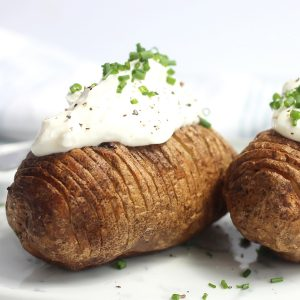 An air fryer hasselback potato topped with sour cream and fresh chives.