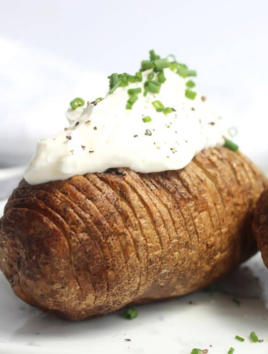 An air fried hasselback potato topped with sour cream and chives.