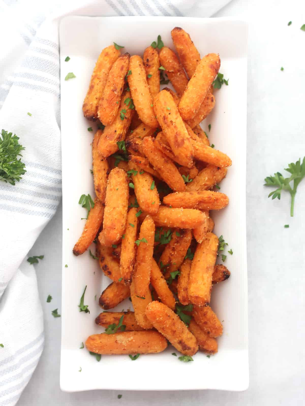 Air fryer carrots on a white serving plate next to a blue and white cloth with parsley garnish.