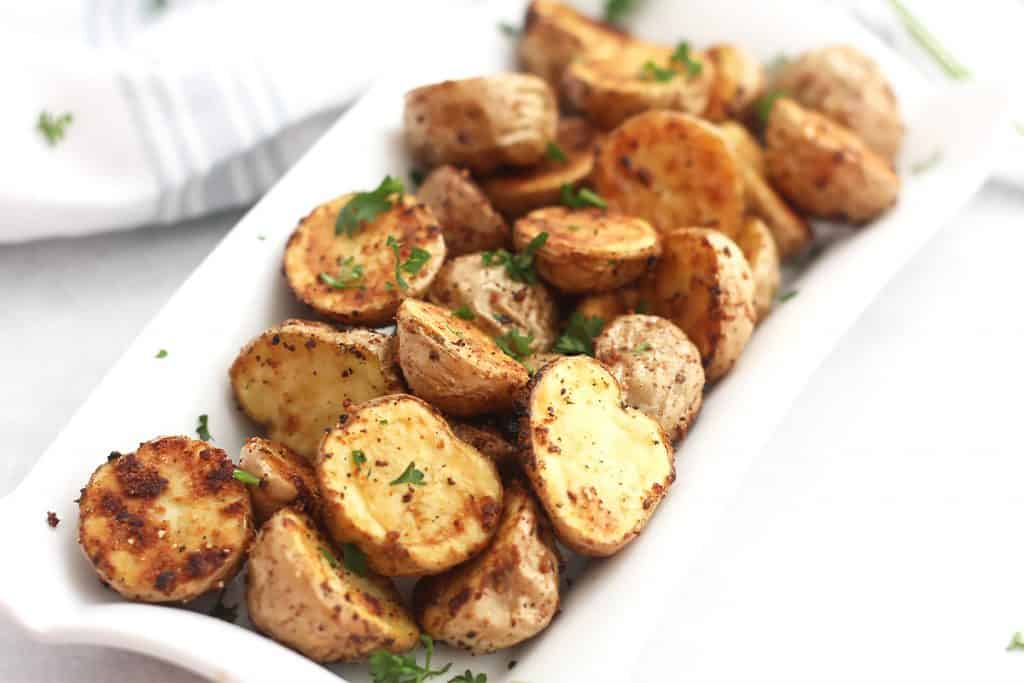 Air fryer baby potatoes garnished with fresh herbs.