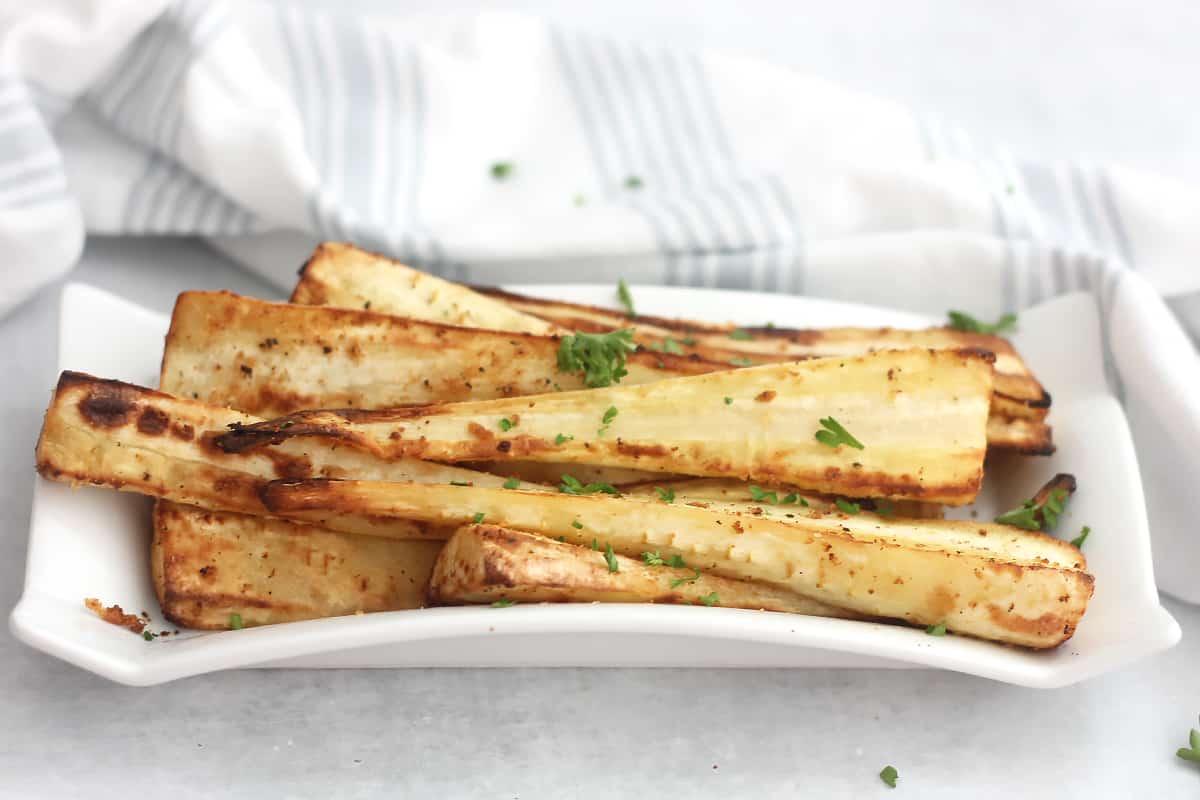 Air fryer parsnips garnished with fresh herbs.