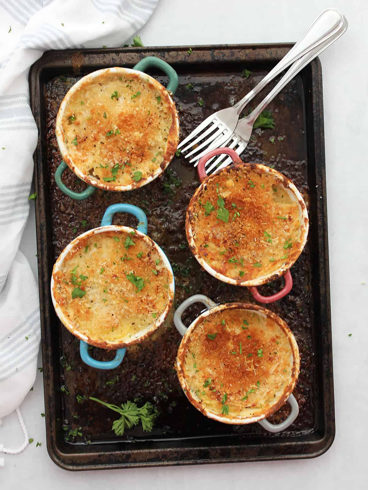 Four individual potato gratins on a baking sheet and garnished with fresh herbs.