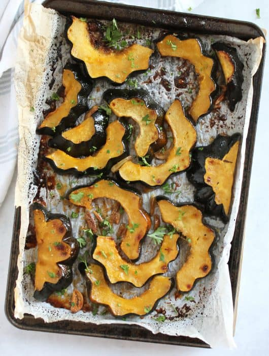 Maple roasted acorn squash on a parchment lined baking sheet.