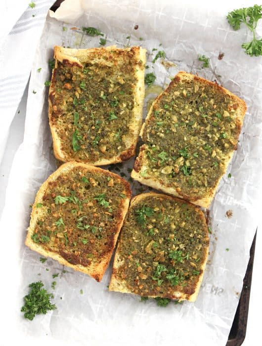 Four pieces of pesto garlic bread on a lined baking sheet with fresh parsley garnish.