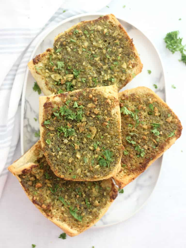 Overhead shot of four pieces of pesto garlic bread on a serving plate.