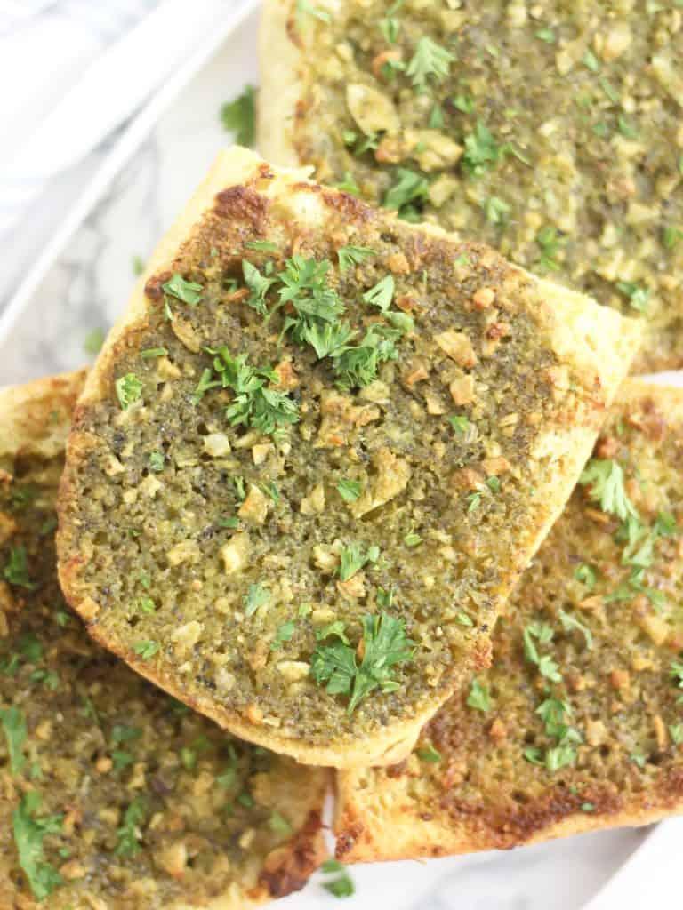 Close up of a pice of pesto garlic bread with parsley garnish.