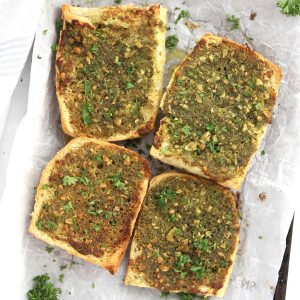 Four pieces of pesto garlic bread on a parchment lined tray.