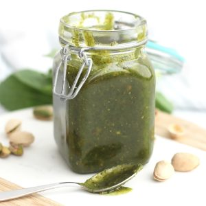 A jar of pistachio pesto next to a spoon that has been dipped in it.