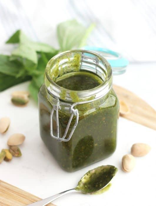 A jar of pistachio pesto next to raw pistachios and basil.