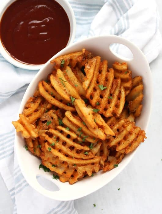 A bowl of air fryer frozen waffle fries next to a BBQ sauce dip.